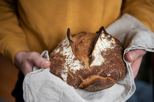 Person holding fresh baked loaf of sourdough bread