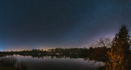 Stores à enrouleur Europe de l Est Belarus, Eastern Europe. Night Sky Stars Above Countryside Landscape With River. Natural Starry Sky Above Lake Pond In Early Spring Night. Russian Nature