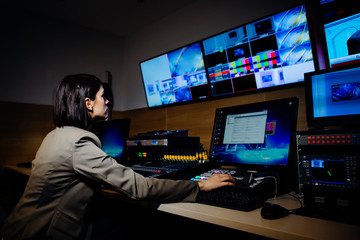 Female TV director control editing room in television studio.Operating vision mixer console equipment in a broadcast panel gallery.Realtime graphic engineer editor.Breaking news headline.Live stream
