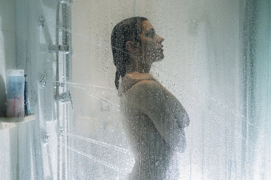 Night shower.Taking relaxing massage shower.Self care moment.Personal hygiene,spa.Unfocused woman showering in glass shower with strong pressure water stream.Focus on drops