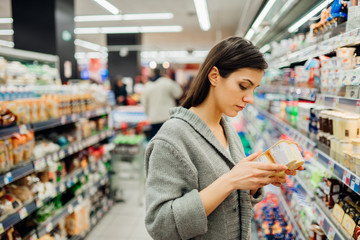 Young woman shopping in the supermarket grocery store.Reading ingredients,declaration or expiration date on a dairy product before buying it.Nutritional values of the food.Lactose intolerance