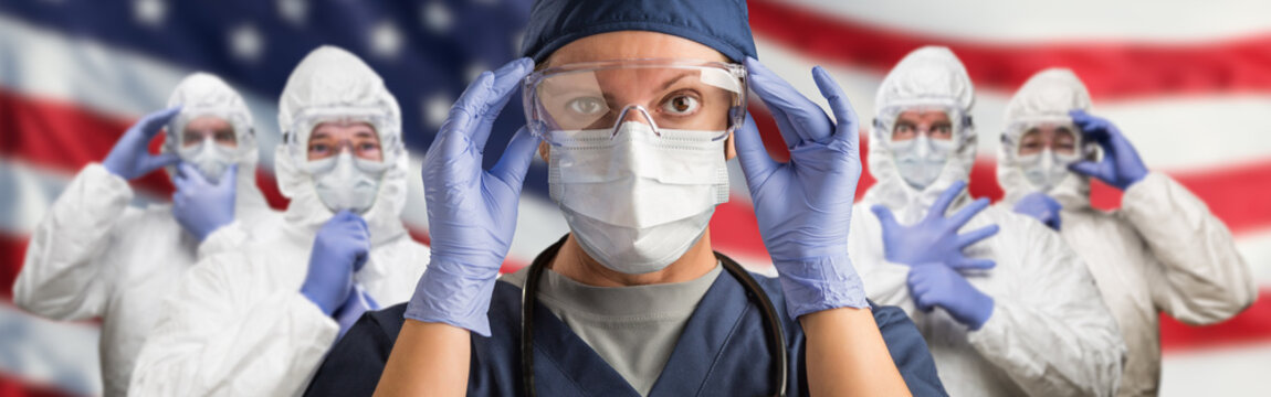 Doctors or Nurses Wearing Medical Personal Protective Equipment (PPE) Against The American Flag Banner