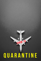 """plane on dark background with text """"quarantine"""" due to the impact of coronavirus concept. Covid-19"""