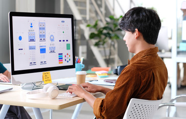 Website designer, Creative planning phone app development template layout framework wireframe design, User experience concept, Young asian man UX designer working on smartphone application at office