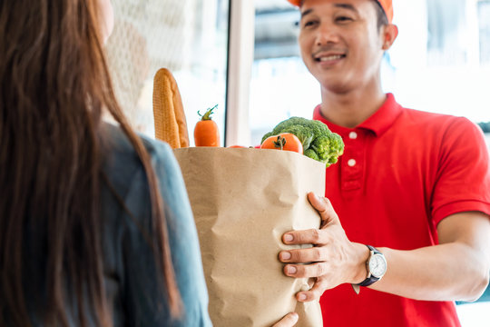 Asian deliver man worker in red color uniform handling bag of food, fruit, vegetable give to young beautiful female costumer in front of the house. Postman and express grocery delivery service concept
