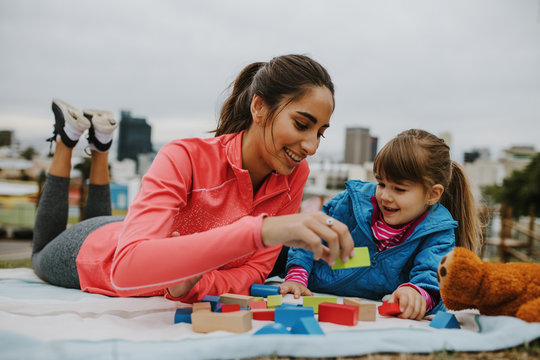 Girl and nanny playing wooden blocks