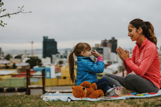 Girl playing patty-cake game with her nanny outdoors