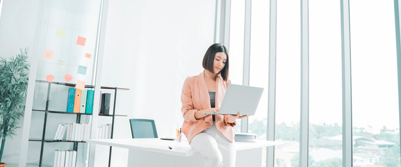Obraz attractive young Asian businesswoman working on a laptop at table in workstation office, Thai girl enjoy browsing for online shopping store with copy space for advertisement, for banner websites - fototapety do salonu