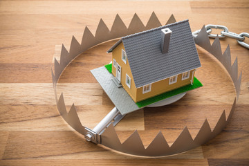 Mortgage house in a trap on wooden table background. House trap on debt or loan problem or risk in real estate property financing concept.