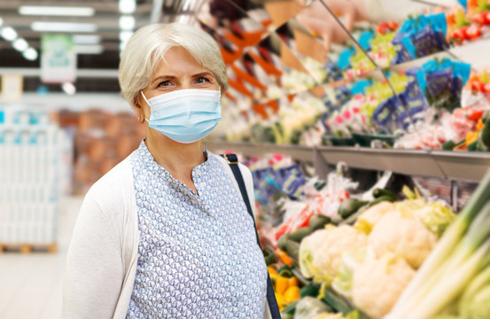 health, safety and pandemic concept - portrait of senior woman in glasses wearing protective medical mask for protection from virus over supermarket background