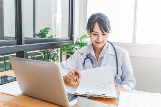 asian female doctor working in hospital office looking and reviewing documentation of forms and contracts of health care, health insurance, diagnosis of patients medical records, using laptop computer