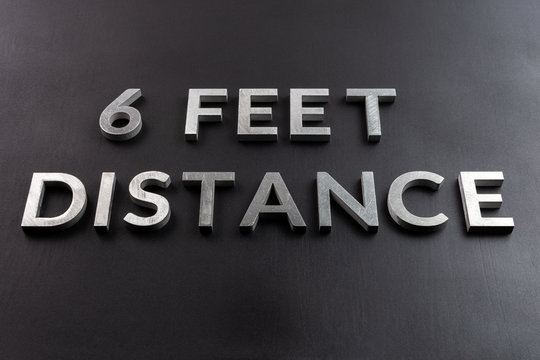 the words 6 feet distance laid with white metal letters on black matte surface in perspective composition