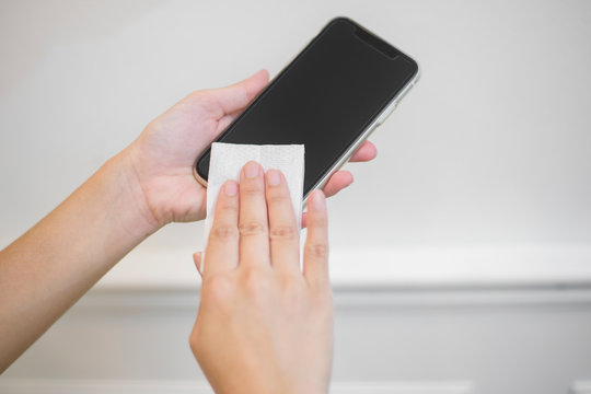 woman is cleaning cell phone