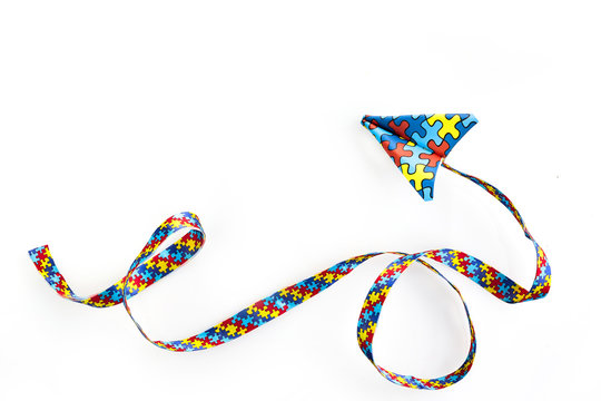 Autism awareness day or month. Paper plane in origami style with autism awareness puzzle ribbon on white background.