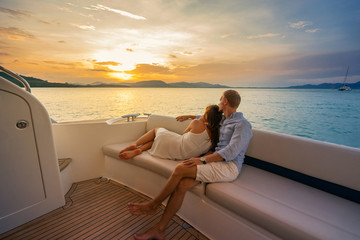 Romantic vacation . Beautiful couple looking in sunset from the yacht. Wall mural