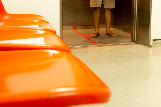 Social distancing red line inside an elevator man standing position for COVID-19 prevention.