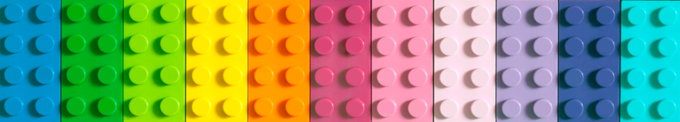 Many toy blocks in different colors making up one large square shape in top view. Toys and games