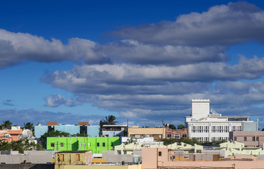 Fototapete - A bright green building in midst of colorful skyline in San Juan under Blue Dusk