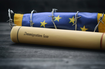 European Union flag, barbed wire and Immigration Law, migration to European Union concept