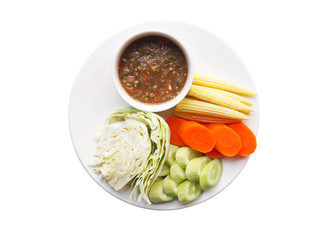 Obraz Top view of thai food with chili paste or nam prik ka pi in cup and boiled vegetables with cabbage, cucumber, carrots and baby corn in dish isolated on white background. - fototapety do salonu