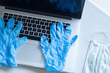 Pandemic work kit on white office desk with face mask and gloves. Corona virus covid-19 pandemic outbreak prevention