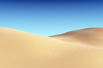 Smooth sand dunes with waves under clear blue sky