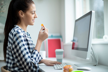 Female Worker In Office Having Healthy Snack Of Dried Apricot Fruit