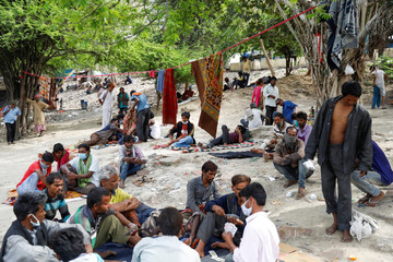 Daily wage workers and homeless people are seen on the banks of Yamuna river near a government-run night shelter during a 21-day nationwide lockdown to limit the spreading of coronavirus disease (COVID-19), in the old quarters of Delhi