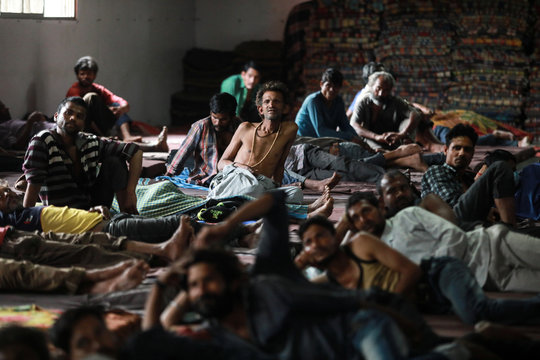 Daily wage workers and homeless people watch television inside a government-run night shelter during a 21-day nationwide lockdown to limit the spreading of coronavirus disease (COVID-19), in the old quarters of Delhi
