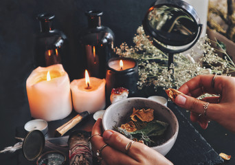 Female wiccan witch holding grey clay pot in her hands preparing ingredients for a spell at her altar. Dried plants, herbs, flowers, lit burning candles, black mirror and old bottles in the background