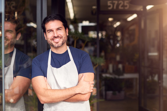 Portrait Of Smiling Male Owner Of Florists Standing In Doorway Surrounded By Plants