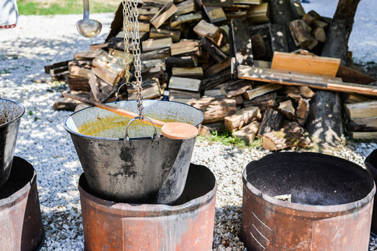 Open-air kitchen with big pot of cooked meal. Pile of woodstocks at the background