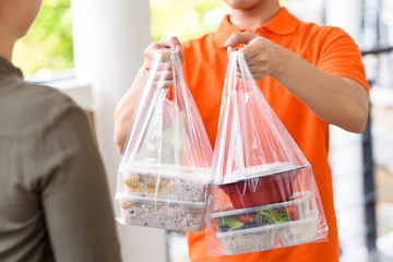 Photo sur Plexiglas Magasin alimentation Delivery man in orange uniform delivering Asian food boxes in plastic bags to a woman customer at home