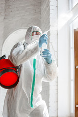 Coronavirus Pandemic. A disinfector in a protective suit and mask sprays disinfectants in house or...