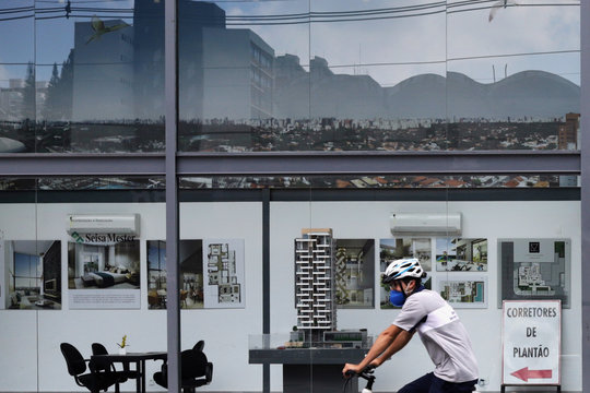 A cyclist using a face mask passes by a sales office of a residential building under construction, amid the coronavirus disease (COVID-19) outbreak, in Sao Paulo