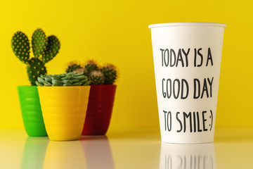Cactus in pot with a paper cup of coffee on wooden desk. Minimal good day concept.