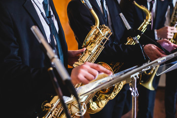 Concert view of a saxophonist, saxophone player with vocalist and musical during jazz band orchestra performing music on stage Wall mural
