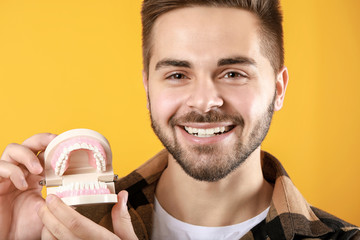 Fotomurales - Happy smiling young man with plastic jaw model on color background