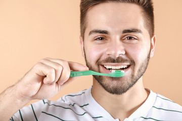 Fotomurales - Happy smiling young man with tooth brush on color background