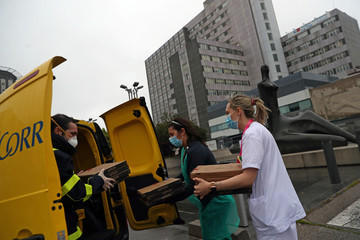 Carrero Castano, a delivery man for the Spanish postal service ÒCorreosÓ, delivers 20 pizzas to medical staff at La Paz Hospital as part of the Food4Heroes initiative during the outbreak of coronavirus disease (COVID-19) in Madrid