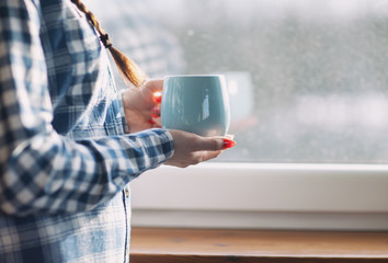 Woman with cup of coffee by the window