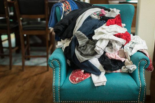 Pile of laundry of clothes on colorful chair in home