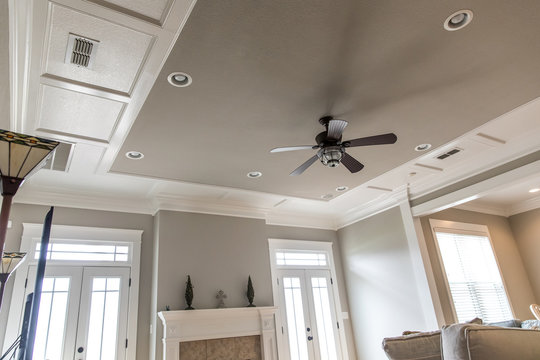 Living room den ornate woodwork tray ceiling with square wood panels painted white and a ceiling fan