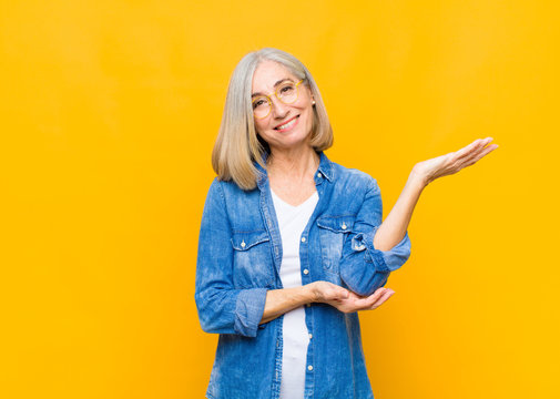 senior or middle age pretty woman smiling proudly and confidently, feeling happy and satisfied and showing a concept on copy space