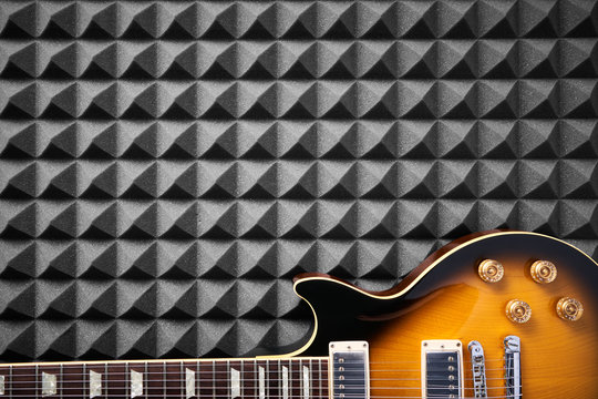 Top view of electric guitar on acoustic foam panel background, closeup