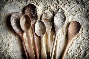 Molti cucchiai di legno cosparsi di farina di grano. Concetto di cottura su sfondo di farina. Effetto filtro fotografico, HDR. Vista dall'alto. Wall mural