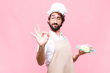 young crazy baker man confectionery concept against pink wall
