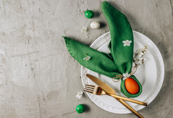 Easter table setting. Empty plates with green linen napkin and golden cutlery on concrete...