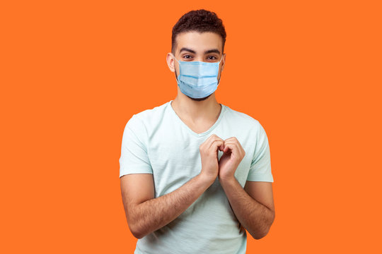 Portrait of joyous handsome brunette man with surgical medical mask in love making heart gesture with hands and smiling broadly at camera,. indoor studio shot isolated on orange background