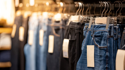Jeans or Denim pants (trousers) hanging on rack in clothes shop. Fashion product collection in clothing store for selling. Textile industry and business concept